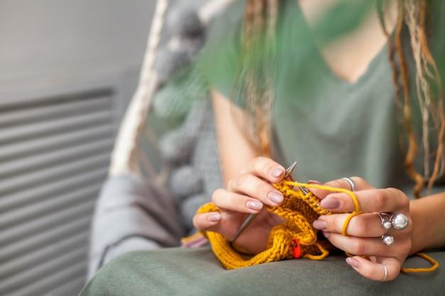 Zbliżenie: kobiece dłonie z dziania. metalowe igły dziewiarskie. żółta dzianina.