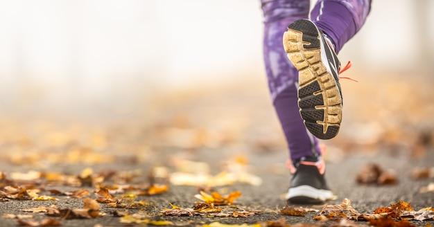 Zbliżenie kobiece nogi i buty do biegania w jesiennej przyrodzie.