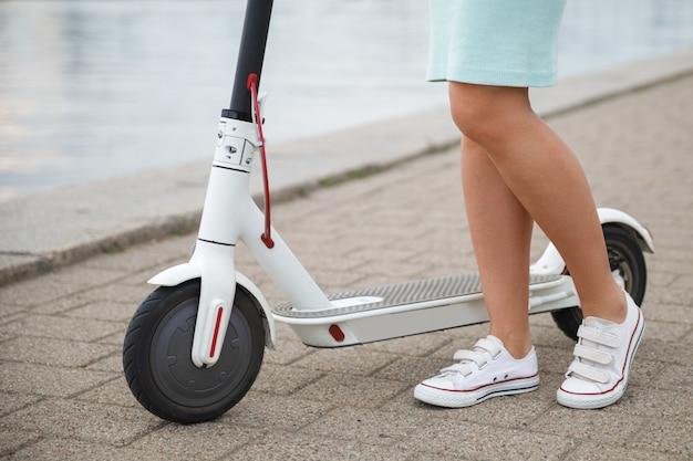 Zbliżenie: kobiece nogi na skuterze elektrycznym