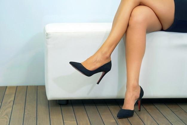 Zbliżenie: kobiece nogi w butach, siedząc na kanapie. nogi kobiety w czarnych butach na wysokim obcasie, kobieta siedzi zrelaksowany na kanapie, koncepcje nogi zdrowia i urody.