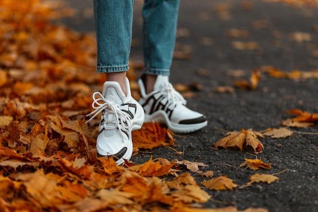 Zbliżenie kobiece nogi w stylowe niebieskie dżinsy w modnych butach