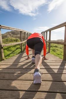 Zbliżenie kobiece nogi z butami do biegania gotowy do rozpoczęcia treningu na tle drewnianej promenady w słoneczny dzień
