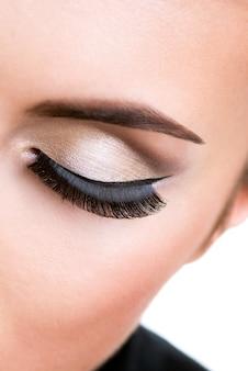 Zbliżenie kobiece oko z piękny makijaż moda z długimi sztucznymi rzęsami.