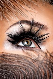 Zbliżenie kobiece oko z pięknym makijażem mody z długimi sztucznymi rzęsami