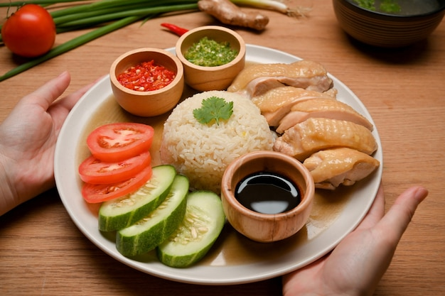 Zbliżenie kobiece ręce trzymając ryż hainanese kurczaka azjatycka pyszne menu uliczne koncepcja