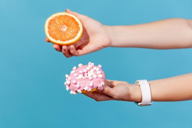 Zbliżenie kobiece ręce trzymając słodki słodki pączek i świeży grejpfrut