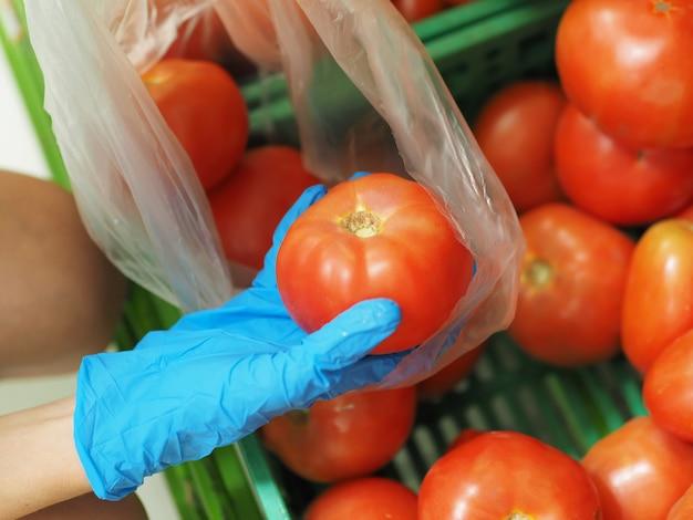 Zbliżenie. kobiece ręce w niebieskich rękawiczkach wybierające pomidora w supermarkecie podczas pandemicznego koronawirusa covid-19.
