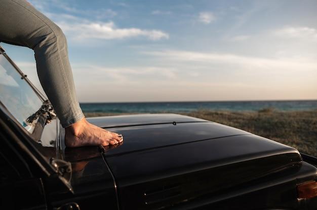 Zbliżenie kobiece stopy leżące na dachu samochodu w świetle słońca. morze na tle.