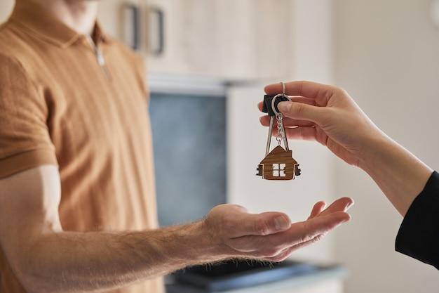 Zbliżenie kobiecego agenta nieruchomości dającego klucze klientowi kupującemu nowy dom, kopia przestrzeń
