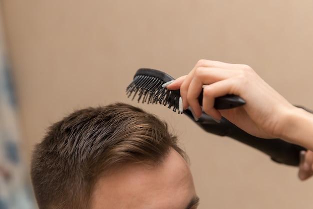 Zbliżenie kobiecego fryzjera suszącego włosy męskiego klienta w jej salonie fryzjerskim