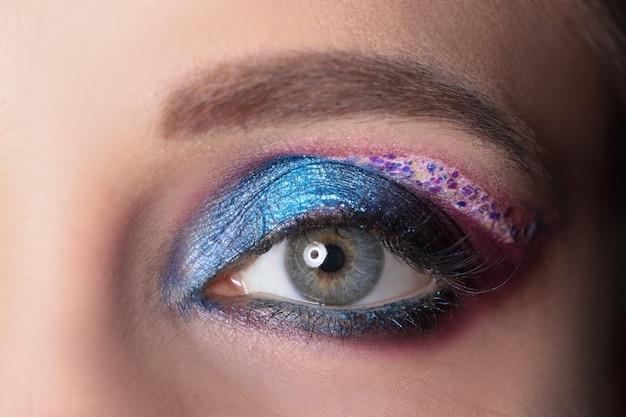 Zbliżenie kobiecego oka z jasnymi błyszczącymi fioletowymi cieniami profesjonalną koncepcją makijażu