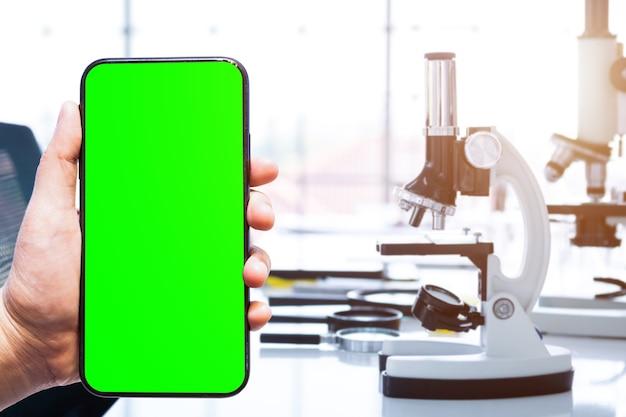 Zbliżenie kobiecego użytku zielony ekran smartfona zamazane obrazy z mikroskopem i probówkami ze szkła laboratoryjnego w tle laboratoryjnym, badania i koncepcja naukowa
