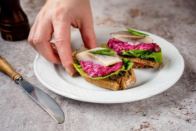 Zbliżenie kobiecej dłoni biorąc kanapkę ze śledziem z buraków i zieloną sałatą z płyty