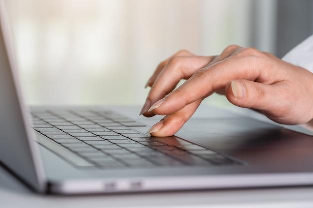 Zbliżenie kobiecej dłoni naciskając przycisk spacji na klawiaturze laptopa