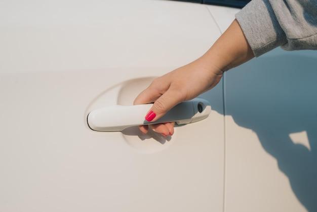 Zbliżenie kobiecej dłoni otwierającej drzwi samochodu