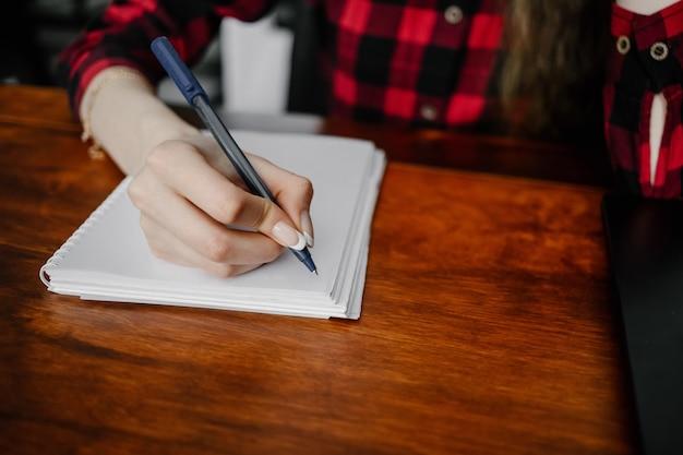 Zbliżenie kobiecej dłoni pisania na papierze