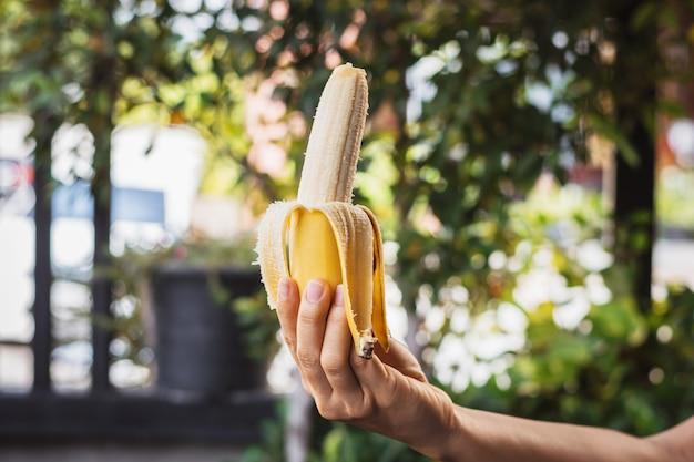 Zbliżenie kobiecej dłoni trzymającej dojrzałego banana z rozmytym tłem parkowym