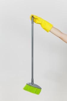 Zbliżenie kobiecej dłoni w żółtych rękawiczkach trzyma długą szarą miotłę z zielonymi kosmkami do czyszczenia i zamiatania na białym tle. koncepcja czyszczenia dostaw. skopiuj miejsce na reklamę.