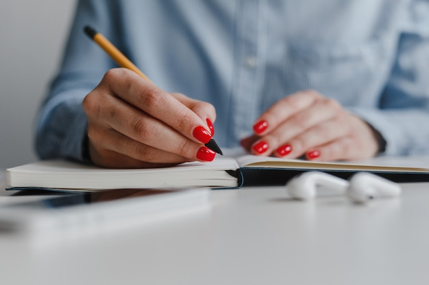 Zbliżenie kobiecej dłoni z czerwonymi paznokciami robienia notatek i białych słuchawek, telefon na biurku