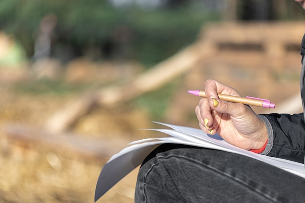 Zbliżenie kobiecej dłoni z żółtym manicure trzyma długopis i arkusze papieru na rozmytym tle na zewnątrz, miejsce.
