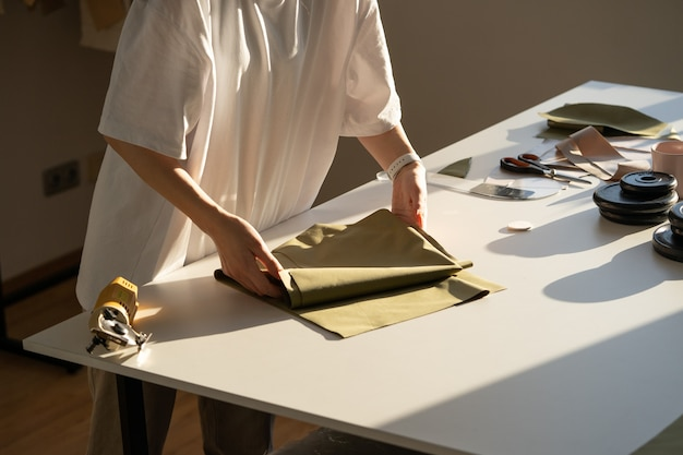 Zbliżenie kobiecej kanalizacji trzymaj tkaninę do cięcia, pracując w procesie twórczym warsztatowym studio w atelier
