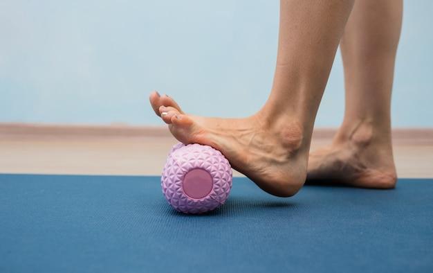 Zbliżenie kobiecej nogi wykonującej masaż masażerem ortopedycznym
