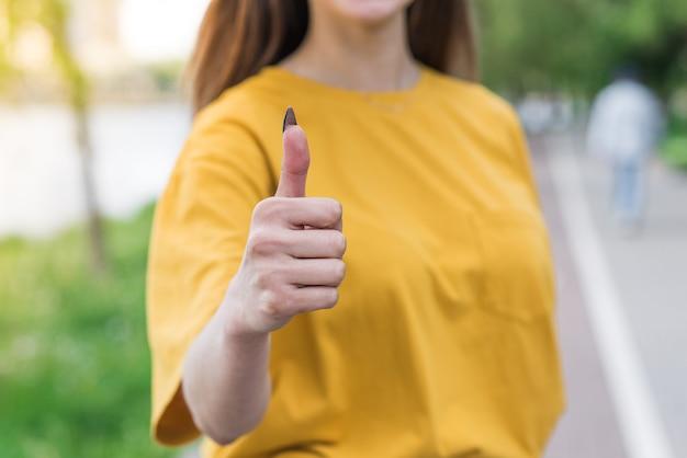 Zbliżenie kobiecej ręki kaukaskiej pokazującej kciuk w górę