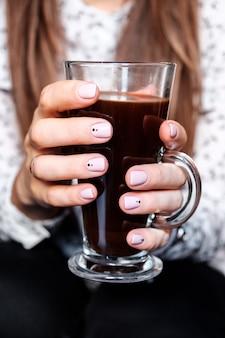 Zbliżenie kobiecej ręki trzymającej filiżankę gorącej kawy.