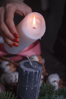 Zbliżenie kobiecej ręki wlewającej stopiony wosk z białej świecy na czarną, świąteczną dekorację wieńca