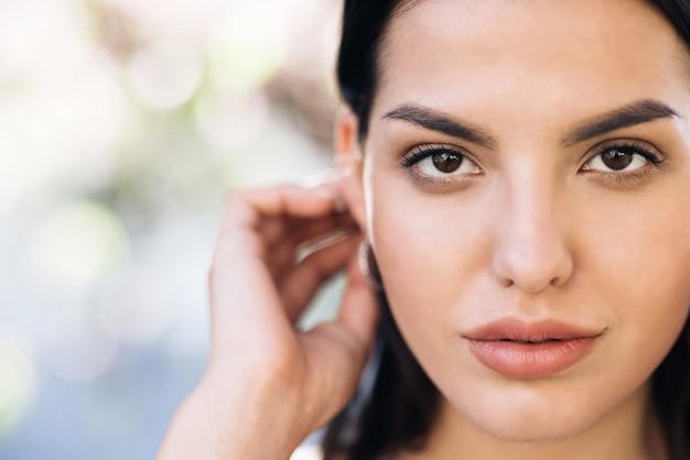 Zbliżenie kobiecej twarzy dziewczyny z jej pięknymi brązowymi oczami naturalne piękno twarzy