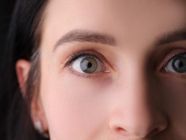 Zbliżenie kobiecych oczu z permanentnym makijażem brwi i sztucznymi rzęsami