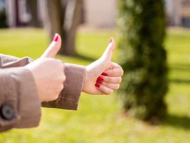 Zbliżenie kobiecych rąk pokazano kciuk znak