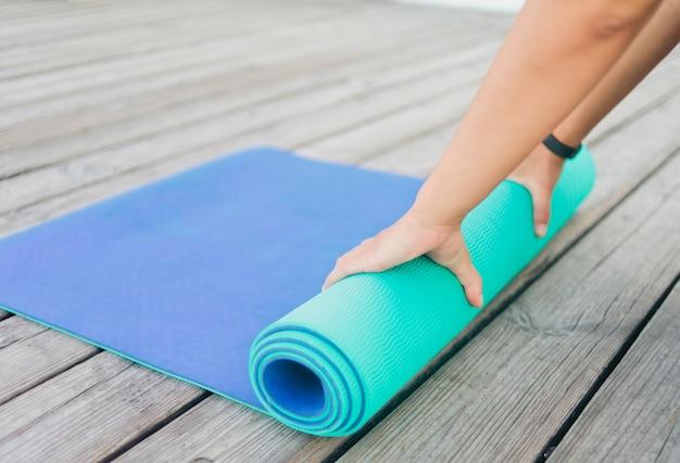 Zbliżenie kobiecych rąk składa mata do jogi na drewnianej podłodze na zewnątrz.