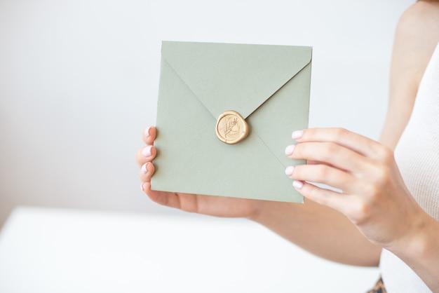 Zbliżenie kobiecych rąk trzymających srebrną niebieską lub różową kopertę z woskową pieczęcią, bony upominkowe, pocztówkę, kartę zaproszenia na ślub.