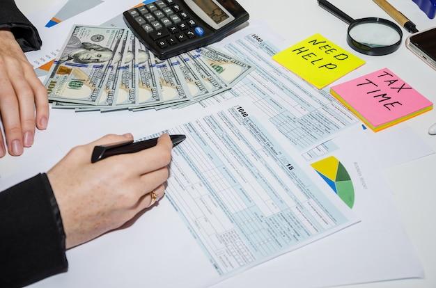 Zbliżenie kobiecych rąk wypełniając formularze podatkowe 1040 koncepcja finansowa