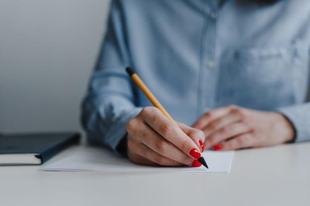 Zbliżenie kobiecych rąk z czerwonymi paznokciami podpisywania i poprawiania dokumentów przy biurku