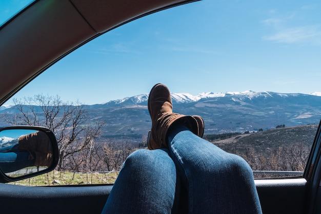 Zbliżenie kobiecych stóp wystających z okna samochodu z pięknym widokiem na góry pod czystym niebem