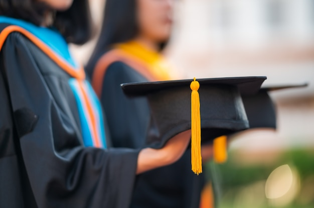 Zbliżenie kobiet absolwentów, absolwentów uniwersytetów, trzymając czarny kapelusz