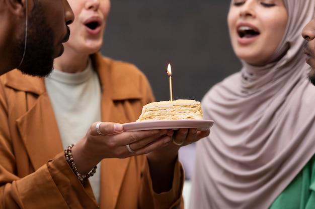 Zbliżenie kobiet dmuchających razem świecę