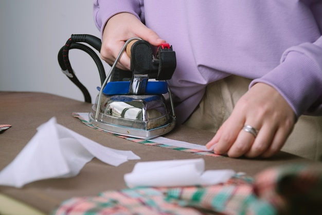 Zbliżenie kobiet do prasowania tkaniny w kratę w szwalni, selektywne focus