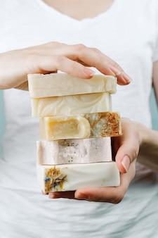 Zbliżenie kobiet ręki trzyma stertę naturalny handmade mydło, selekcyjna ostrość