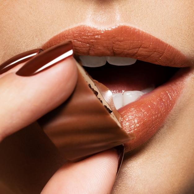 Zbliżenie kobiet usta z brązowymi cukierkami w pobliżu ust.