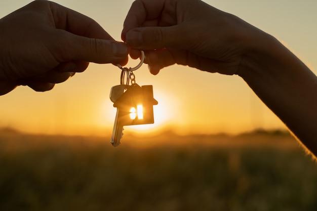 Zbliżenie kobieta daje mężczyźnie klucz do nowego domu na tle pięknego zachodu słońca koncepcja...