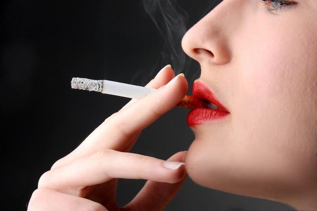 Zbliżenie kobieta dymi papieros