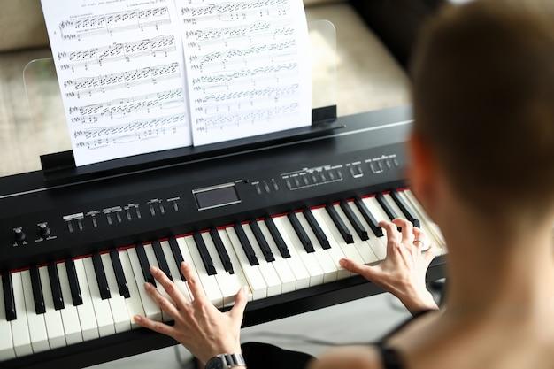 Zbliżenie: kobieta gra na elektrycznym instrumencie fortepianowym. czarno-biały klucz. nuty z piosenką. młoda kobieta ćwiczenia w domu. koncepcja wolnego czasu i hobby