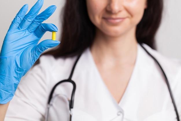 Zbliżenie kobieta lekarz trzymając pigułkę dla zdrowia mężczyzn.