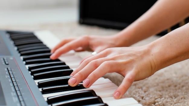 Zbliżenie: kobieta muzyk grający na klawiaturze fortepianu
