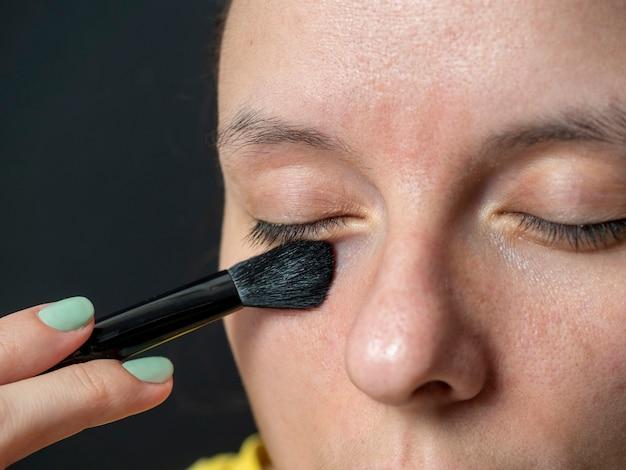 Zbliżenie: kobieta nakładająca cień pędzla na powieki. makijaż w domu, uroda