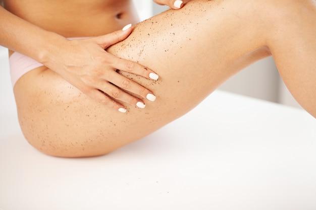 Zbliżenie kobieta nogi z peelingiem do masażu kawy.