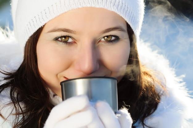 Zbliżenie: kobieta o brązowych włosach, ubrana w białe zimowe ubrania z futrem, pije gorący napój z metalowego kubka
